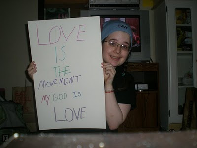 "Image is of me holding up a sign with words written in many colours. The words say ""LOVE IS THE MOVEMENT. MY GOD IS LOVE."""