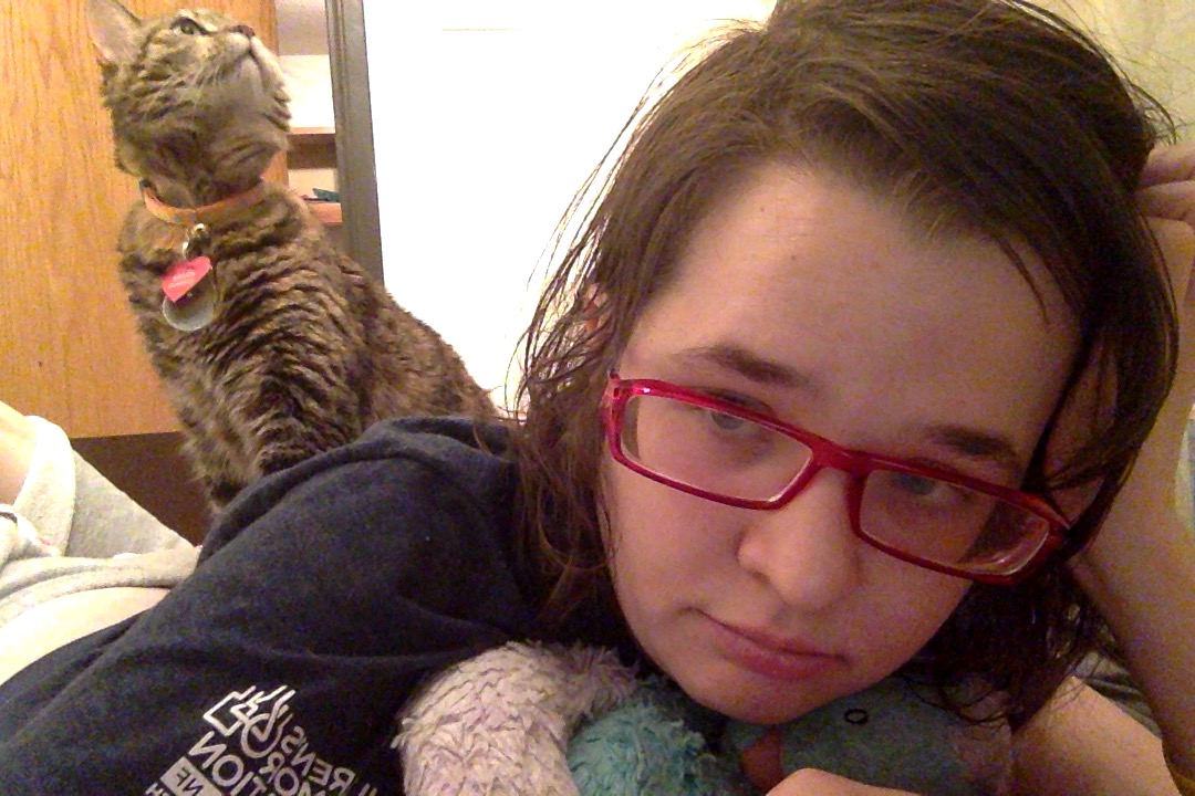 Image is of me wearing my reading glasses, plopped sickly on the bathroom floor with my golden torbie-kitty Athena plopped on my back.