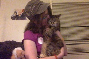 Image description: A young, female presenting person wearing a purple shirt and a brown hat. She is planting a kiss on a very grumpy golden brown tabby.