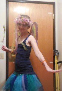 image is of a young looking white female presenting person. she is wearing a navy tank top, and a sparkly navy, medium blue, teal, and purple tutu. she is also wearing purple and green butterfly wings, and has on a pink and purple floral crown. i have no idea how you would describe my position - I leapt back because i forgot to hit the self timer so i was caught in action. almost flailing.