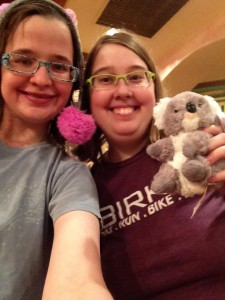 Image: Me, wearing a blue t shirt and a hat and Anna, wearing a purple Birkie t-shirt and holding the koala I got her in Adelaide. We are both smiling at the camera.
