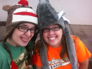 Image description: Me wearing a sock monkey hat and a Muppets t shirt, sticking out my tongue and Anna wearing an Elephant hat and a bright orange Northwestern Eagles T-shirt. She is grinning at the camera.