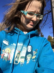 Image is of a pale brunette wearing blue glasses. She is wearing a sweatshirt with various Studio Ghibli characters on it. She is disabled, autistic, asexual, and aromantic - and bloody proud of her labels.