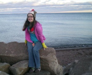 Image is from a few years ago. A pale brunette is sitting on a rock by a lake. She is wearing a sock monkey hat, a purple sweatshirt, a blue T-shirt, and jeans. She also has on yellow wrist warmers.