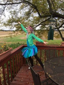Image is a brunette female. She is wearing a green sweater, a blue t-shirt, a blue and green tutu, black tights, and silver shoes.