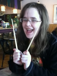 Image is a brunette female holding chopsticks.