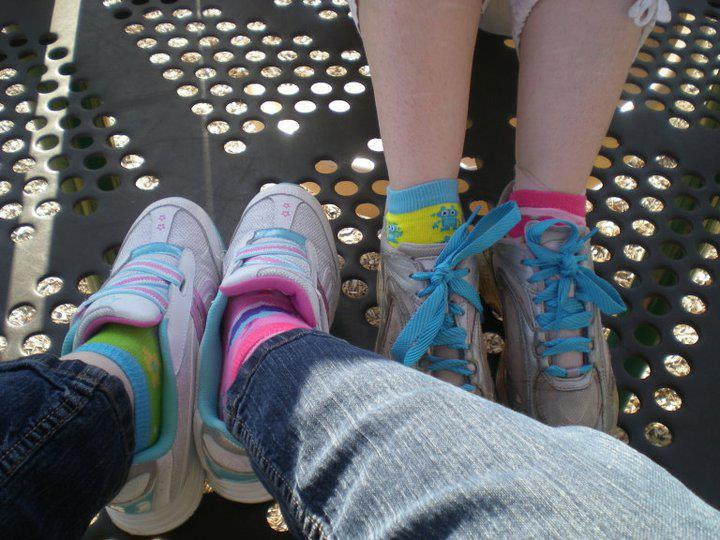 Image: two pairs of feet and two pairs of shoes. Both are rainbowy and fun.