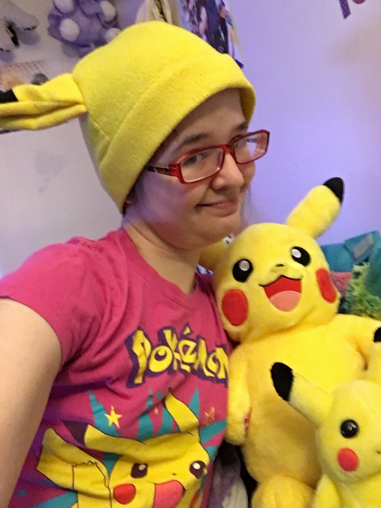 Image is of a brunette female with short hair and red glasses. She is wearing a Pikachu hat, a pink Pikachu t-shirt, and has two stuffed Pikachus in front of her.